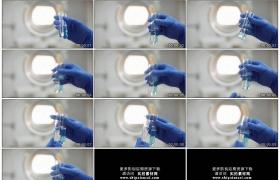 4K实拍视频素材丨特写戴着蓝色手套的女科研人员摇动两只装着试剂的试管