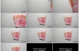 高清实拍视频素材丨特写将一沓人民币放到桌面上