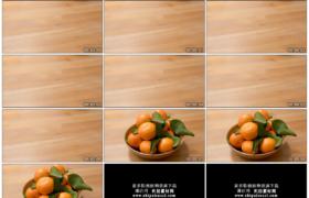 4K实拍视频素材丨在木桌上将一盘新鲜的桔子推到镜头前