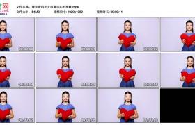 高清实拍视频丨微笑着的小女孩展示心形抱枕