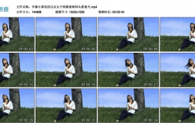 高清实拍视频丨手捧小黄花的白衣女子倚靠着树仰头看着天