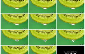 高清实拍视频素材丨绿色背景前切开的猕猴桃片滴落水汁