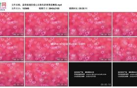 4K动态视频素材丨晶莹剔透的爱心从粉色的背景前飘落