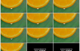 高清实拍视频素材丨绿色背景前切开的橙片滴落水汁