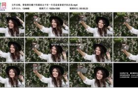 高清实拍视频素材丨带着黑色帽子的漂亮女子在一片花朵前拿着手机自拍