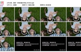 高清实拍视频丨摇摄一对情侣躺在草地上听音乐