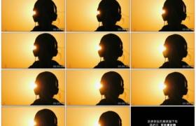 4K实拍视频素材丨特写黄昏天空背景前夕阳逆光中戴着耳机听音乐的人物剪影
