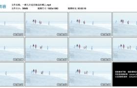高清实拍视频丨一群人行走在海边沙滩上