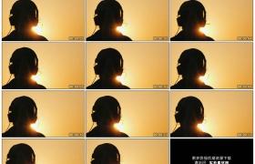 4K实拍视频素材丨特写黄昏天空前夕阳逆光中戴着耳机听音乐的人物剪影