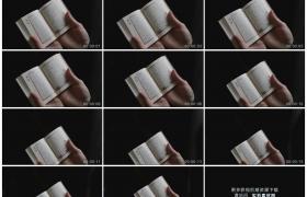 高清实拍视频素材丨特写黑色背景前双手拿着翻开的古兰经