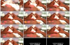 4K实拍视频素材丨特写在夜晚模糊的车灯背景前两只手做出心形手势