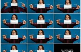 4K实拍视频素材丨蓝色背景前女子展示口罩