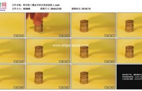 4K实拍视频素材丨特写将三摞金币依次放到桌面上