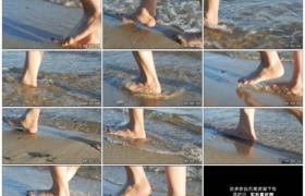 高清实拍视频素材丨低角度跟随拍摄女子光着脚行走在波浪轻抚的沙滩上